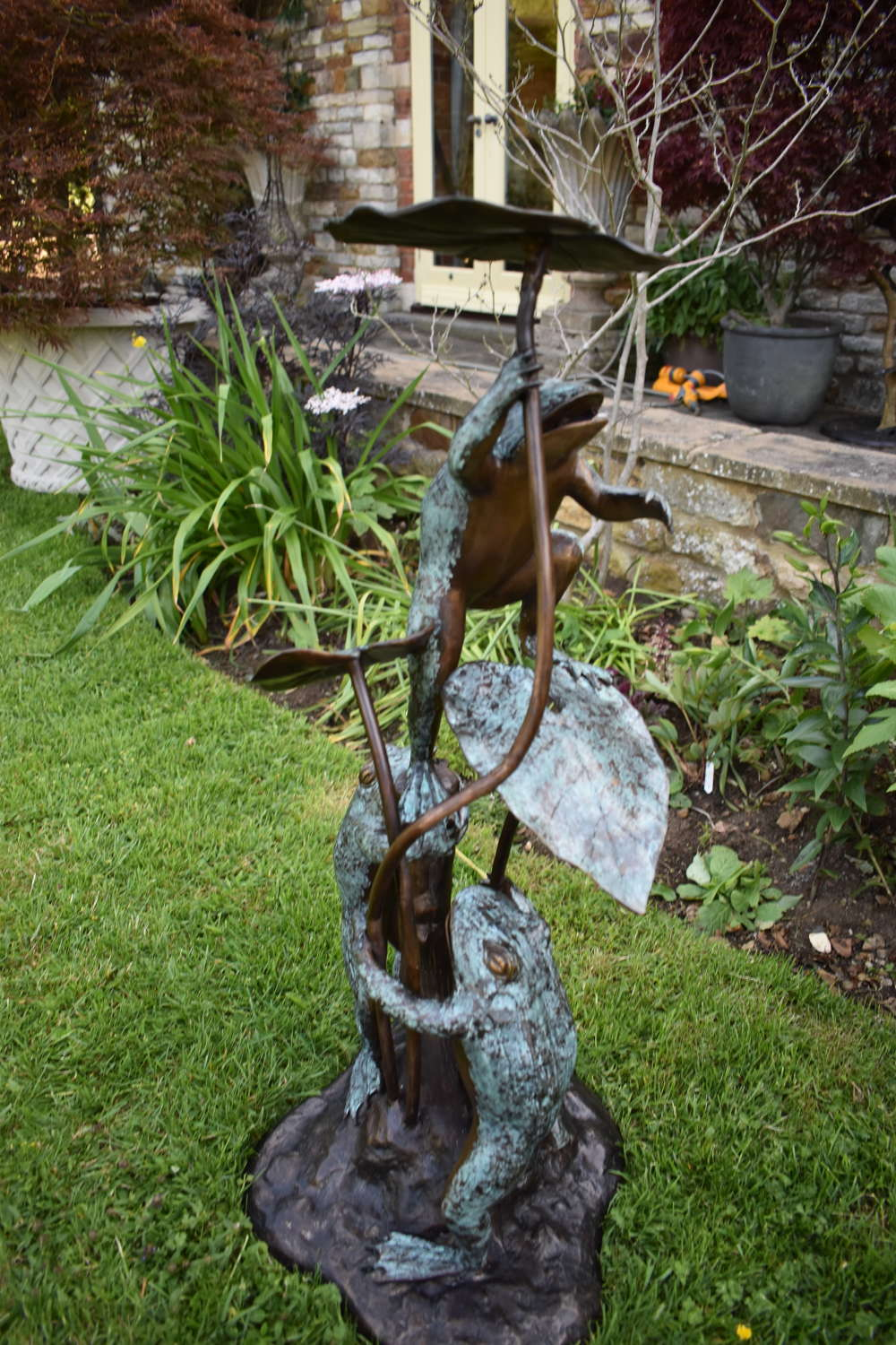 Bronze statue of three frogs on water lily - water feature