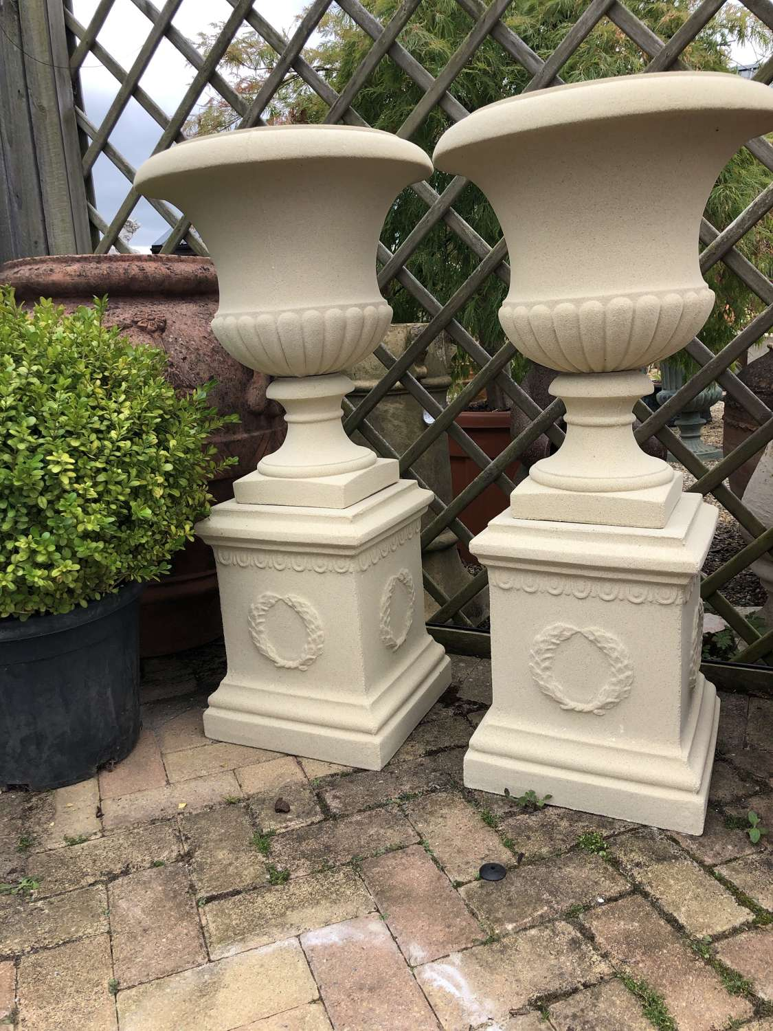 Pair of stone urns on sq plinths 94 cm