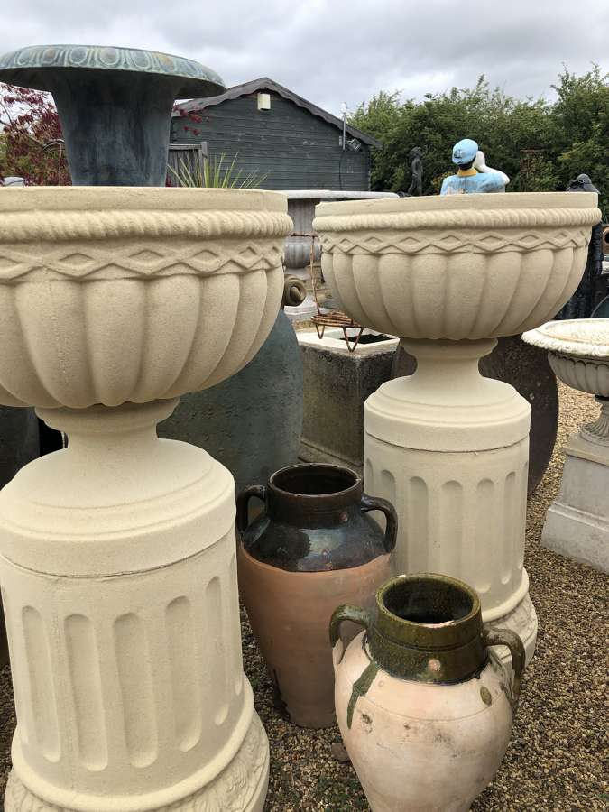 Pair of stone urns on columns 99 cm tall