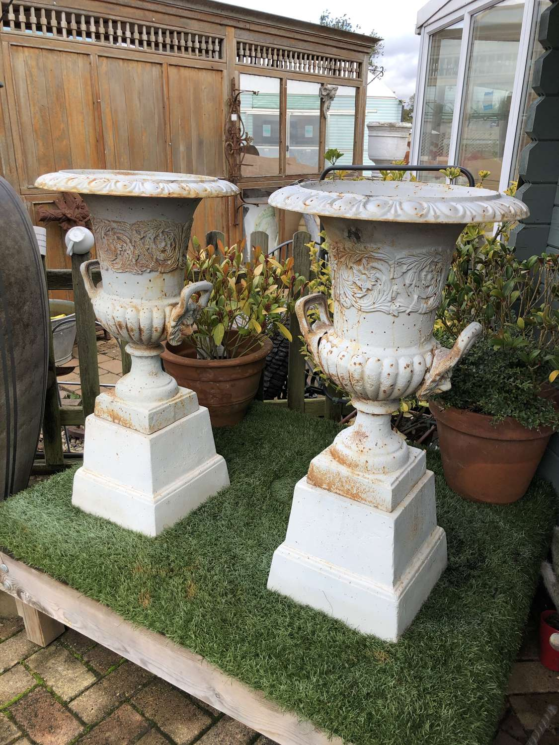 Pair of rusty white campagna urns (with handles) & plinths