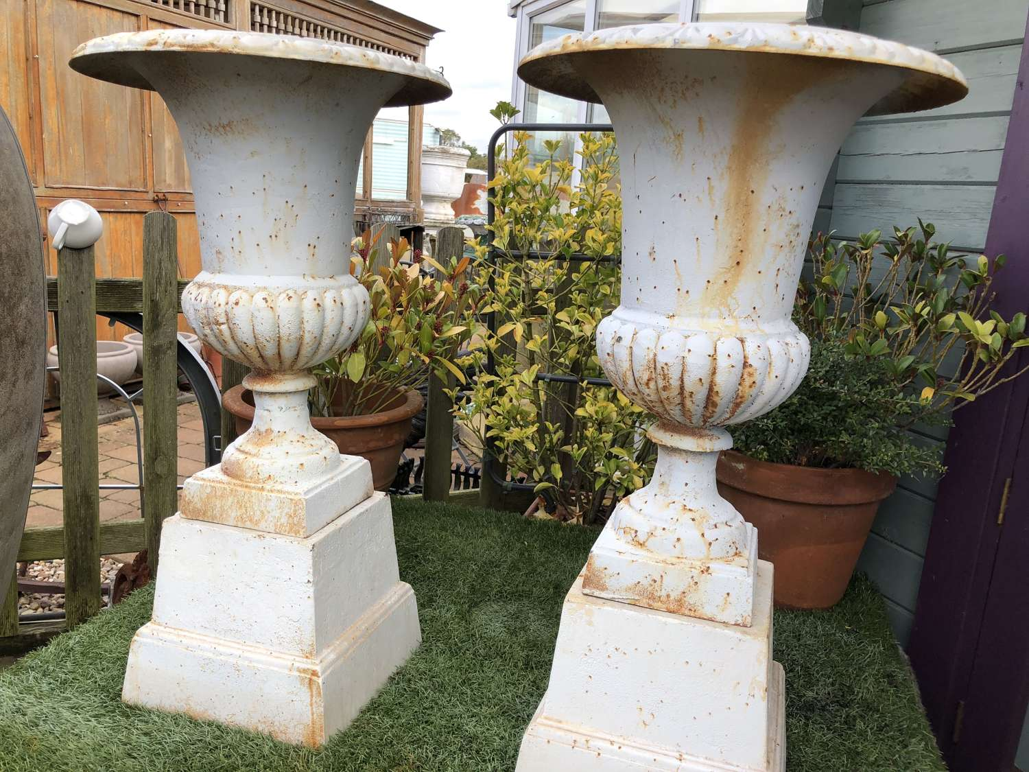 Pair of cast iron campagna urns & plinths