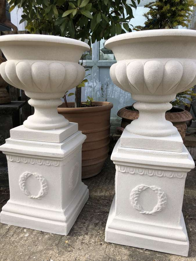 Pair of Gadrooned stone urns on plinths (Portland Colour)