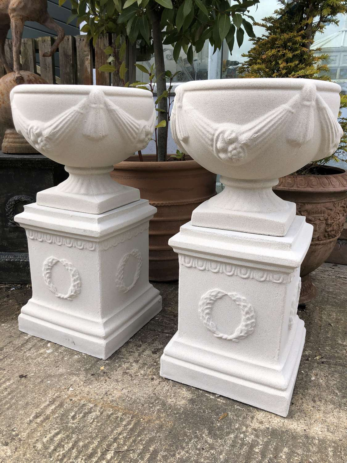 Pair of swagged stone urns on plinths (Portland colour)